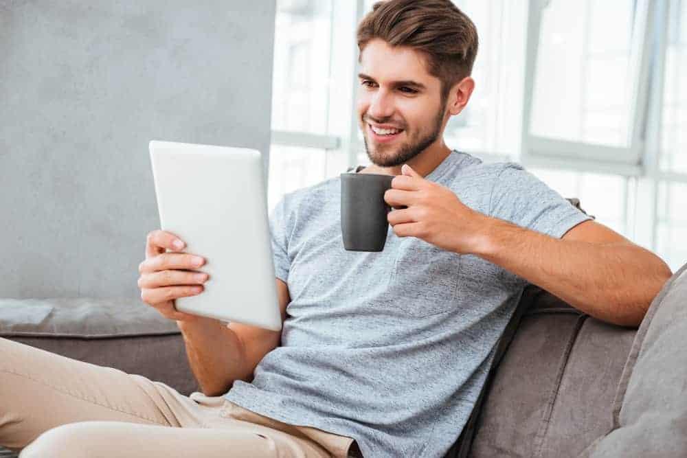 A man wearing slacks and shirt on the sofa.