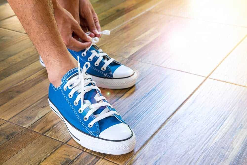 A man putting on his blue canvas sneakers.