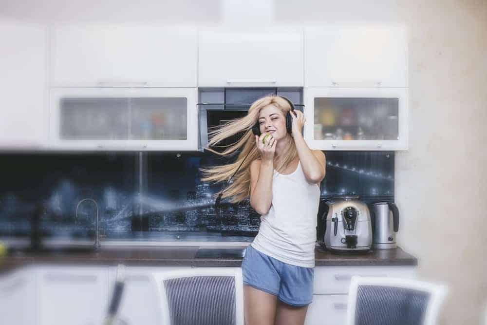 A woman dancing around in her kitchen wearing loungewear.