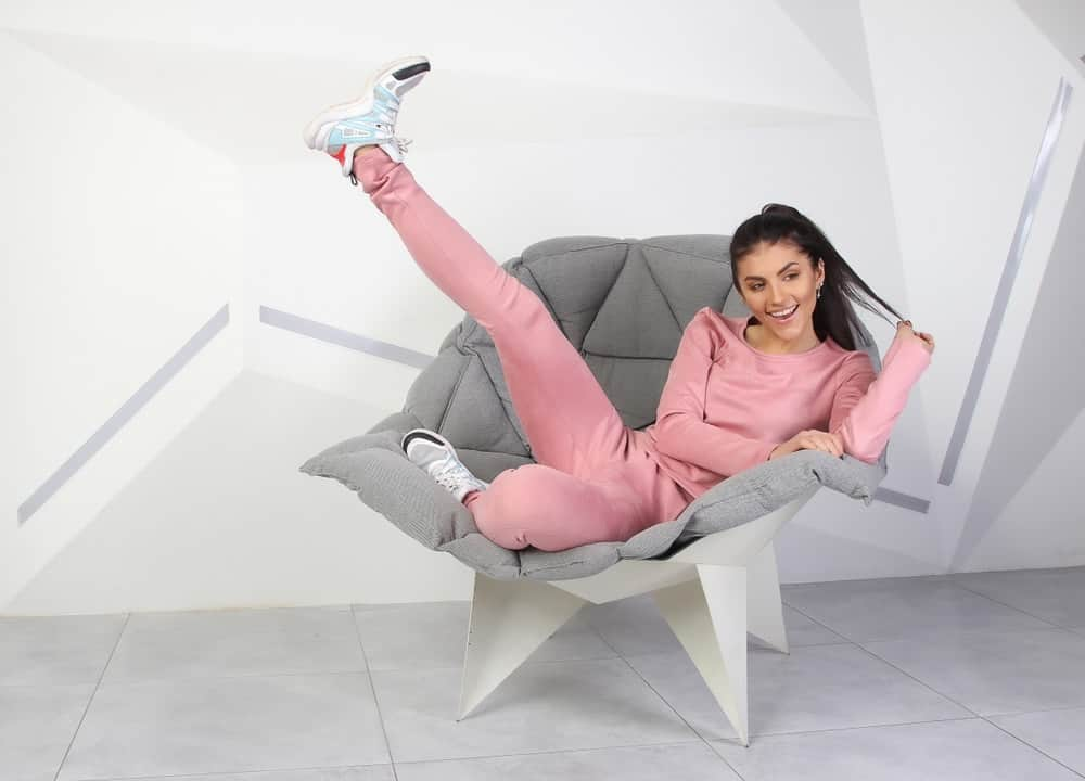 A woman lounging at home wearing a pair of pink tracksuit.