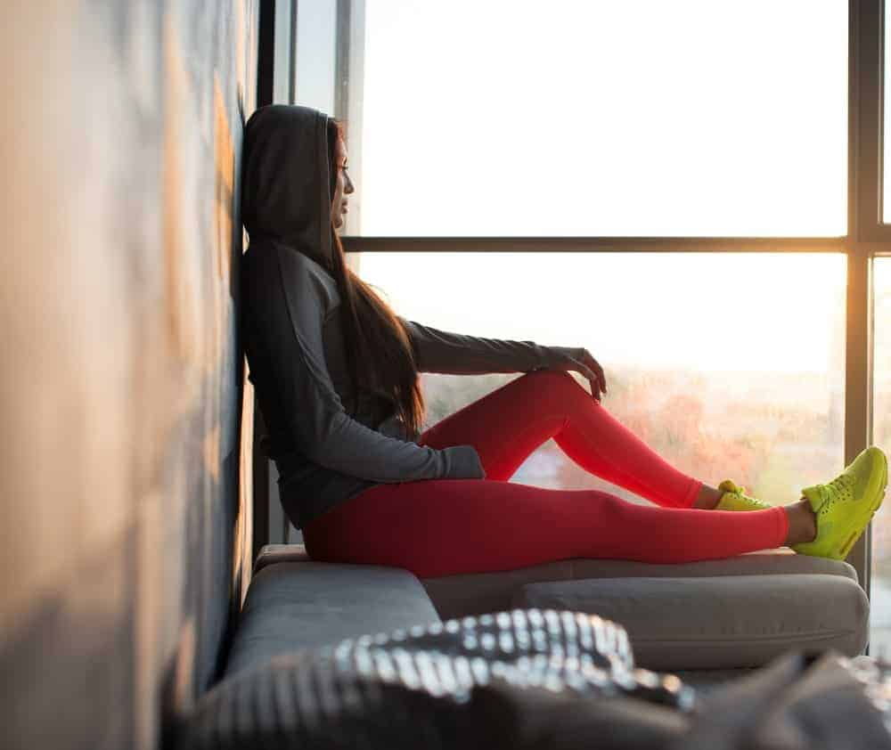 A woman wearing a pair of bright leggings relaxing by the window.