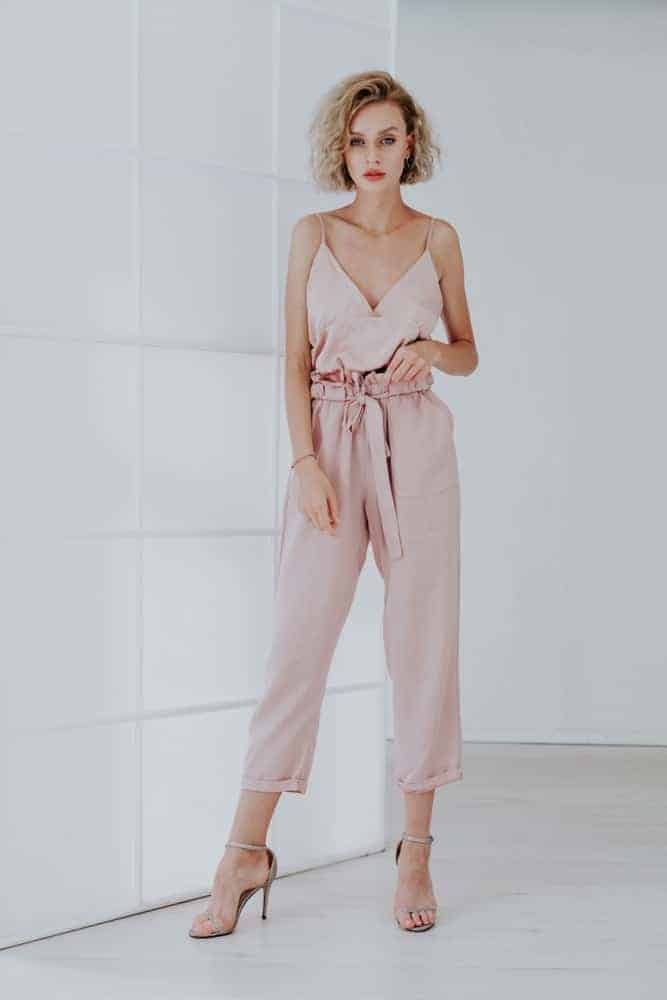 A woman wearing a pair of fashionable pink jumpsuit.