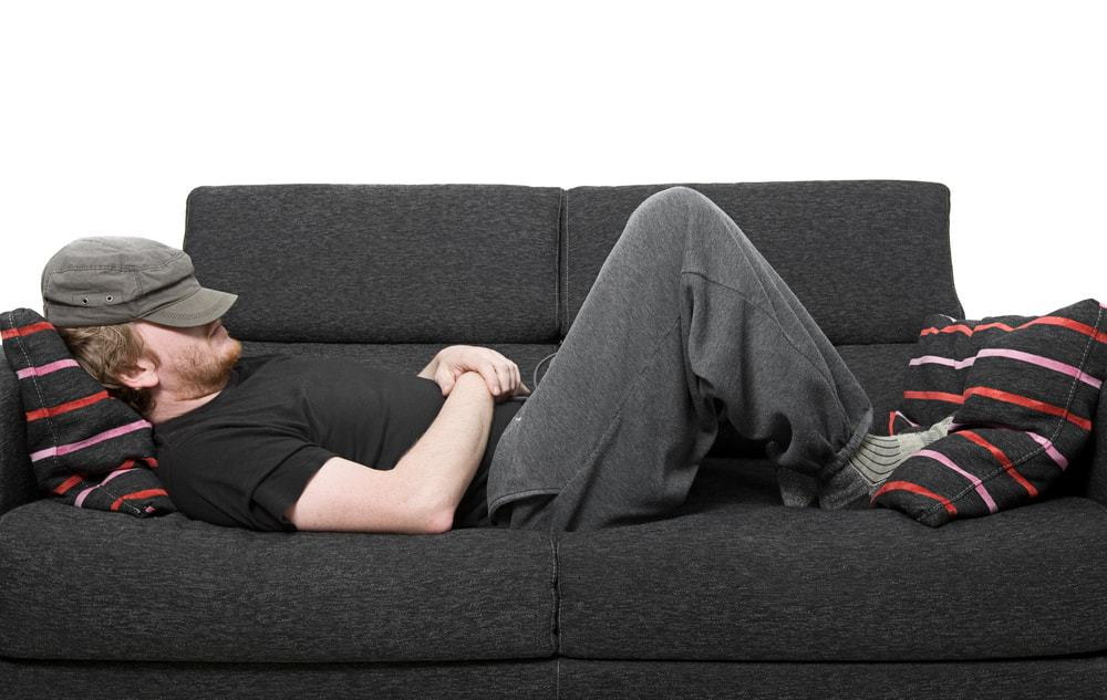 A man wearing sweatpants asleep on the couch.
