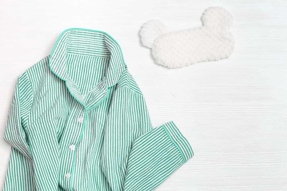 A pair of mint-colored pajamas with a white sleeping mask.