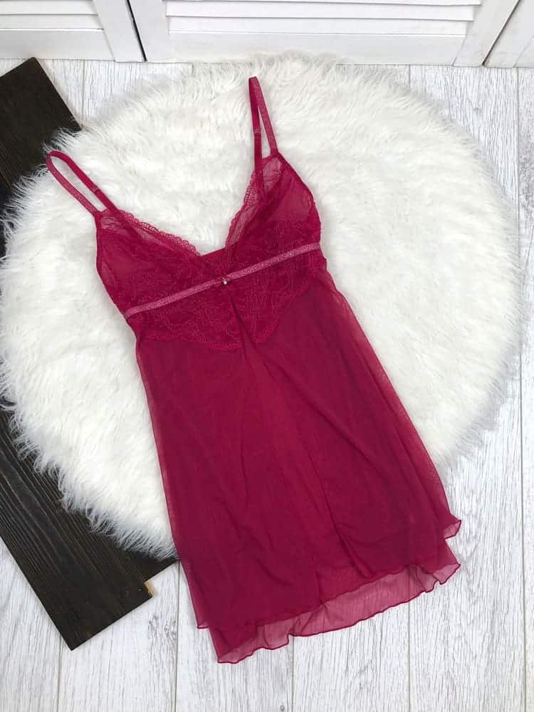 This is a close look at a pair of pink lace nighties on a white area rug.
