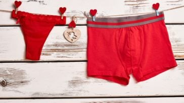 A pair of red panties and a pair of red boxer briefs on a wooden surface.