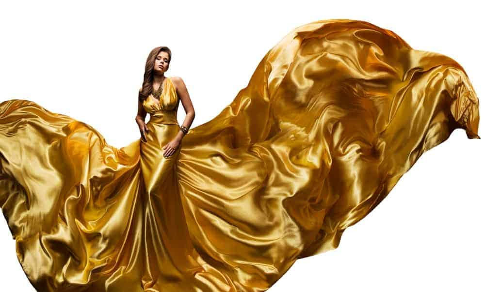 A woman wearing a large golden dress that billows with the wind.