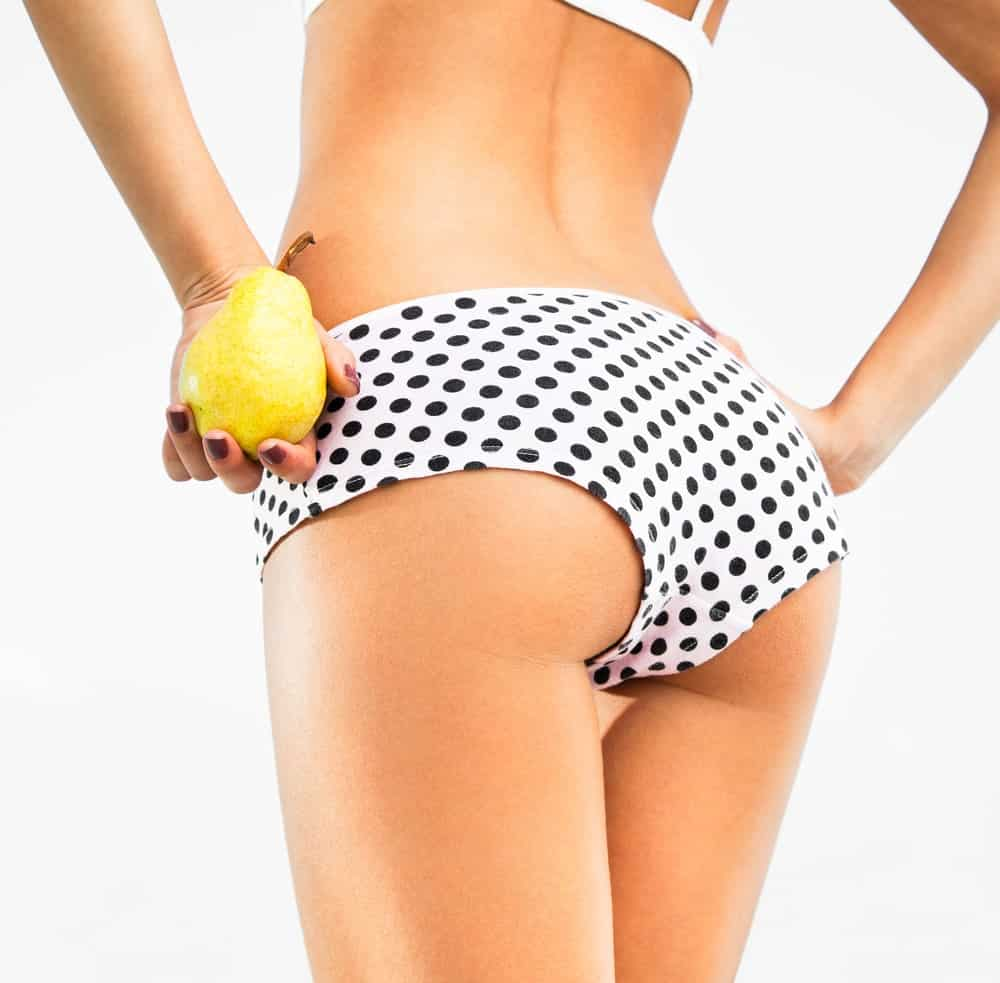 A pear-shaped woman wearing a black and white bikini seen from behind.