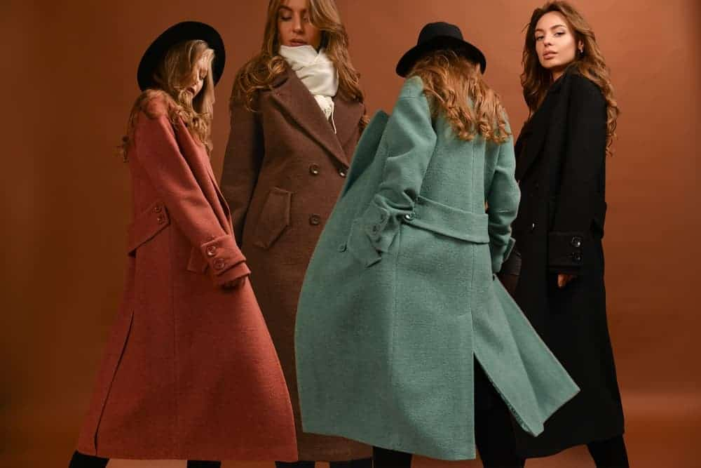 A group of women wearing different long coats.