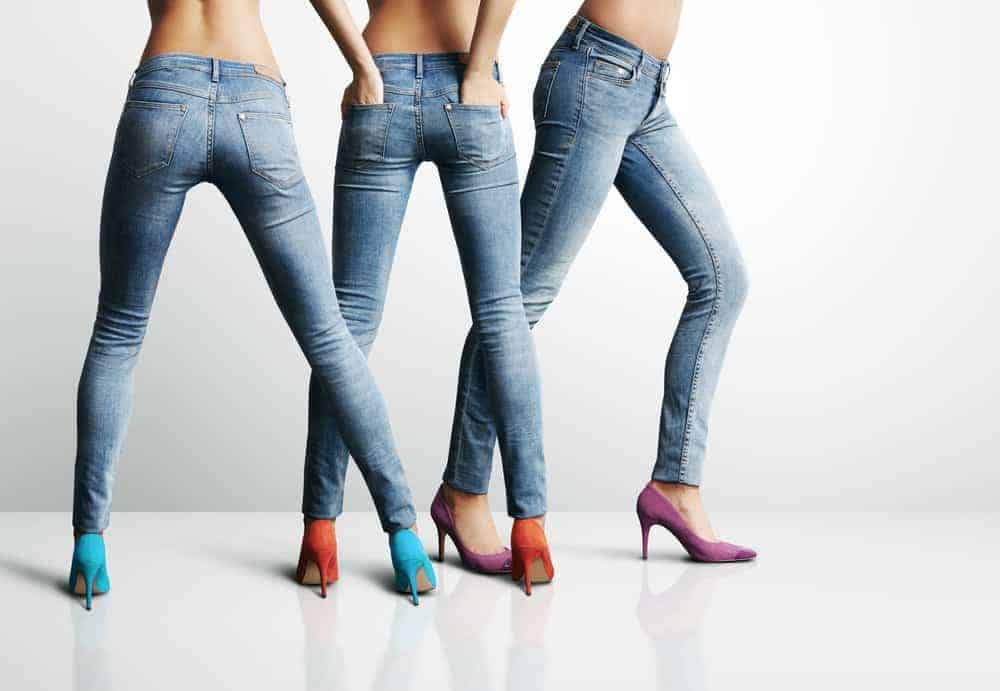 Three women wearing jeans and colorful shoes.