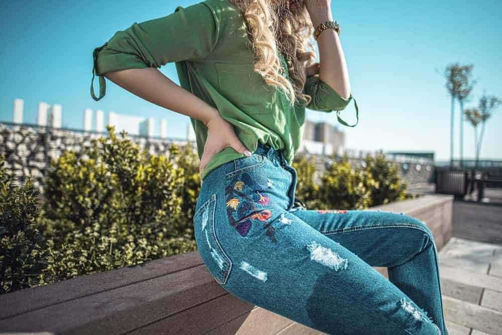 A woman wearing a pair of jeans and green blouse at the park.