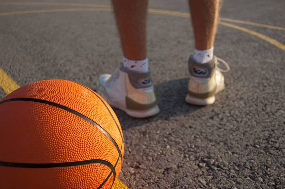 Orange basketball and player's legs on an outdoor court.