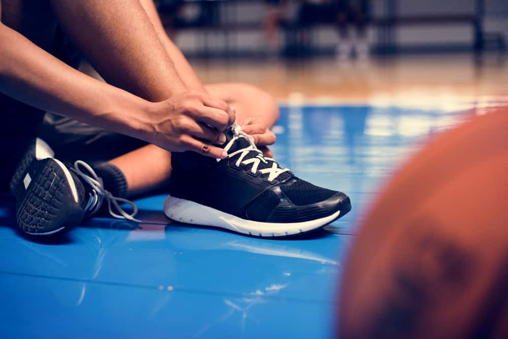 Player tying his shoe laces on a basketball court.