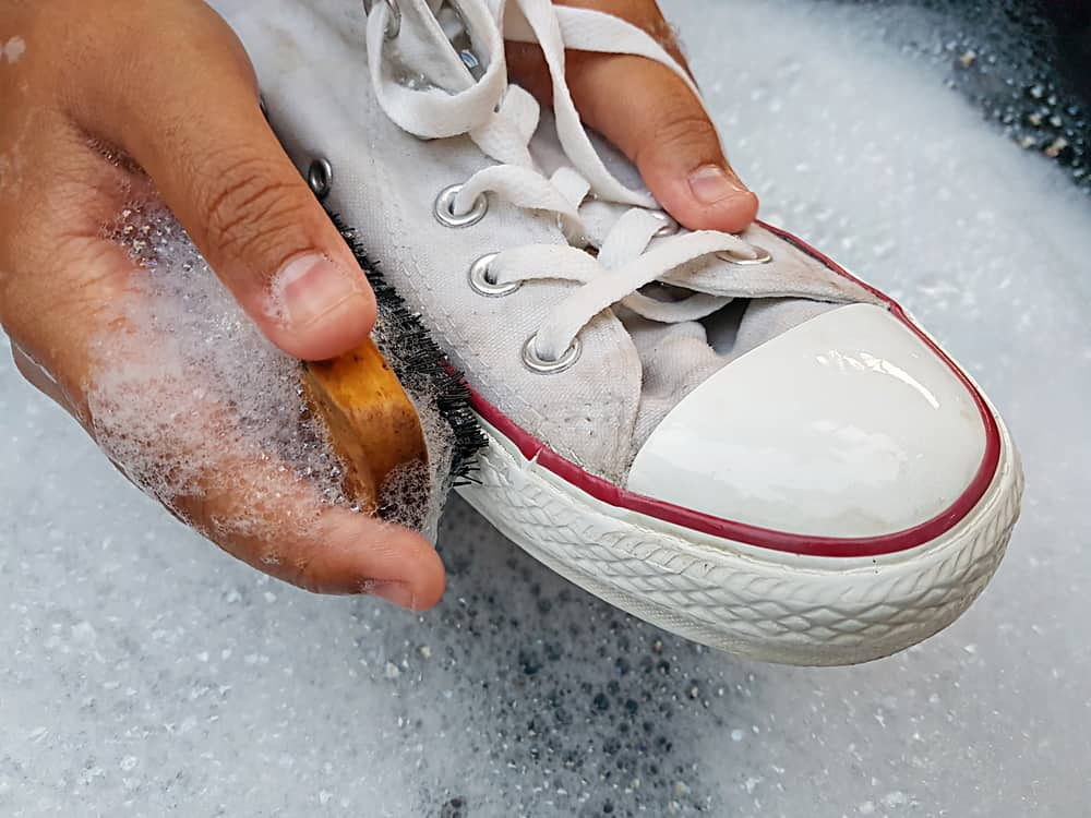 Cleaning white sneaker with soapy water.