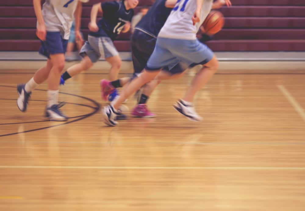 Team running down the court during basketball game.