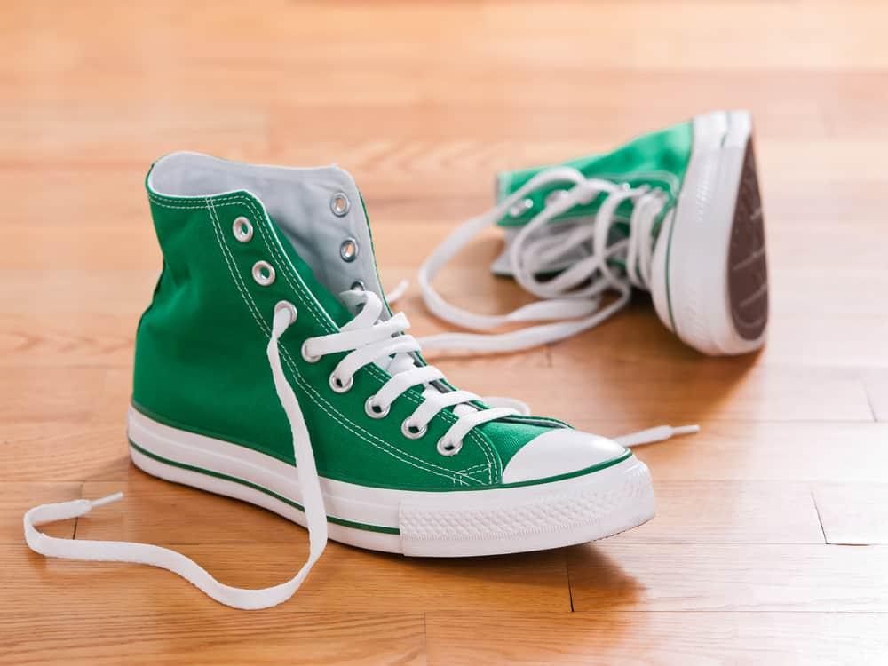 Green high cut sneakers on wooden floor.