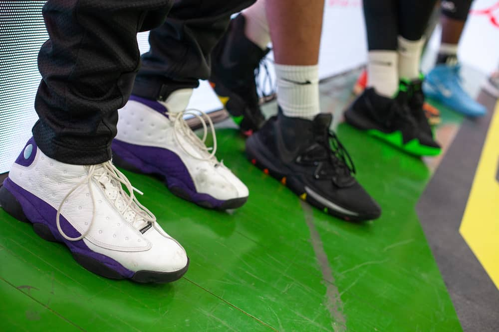 Jordan 13 Retro Lakers basketball shoes on parquet floor during a professional match.