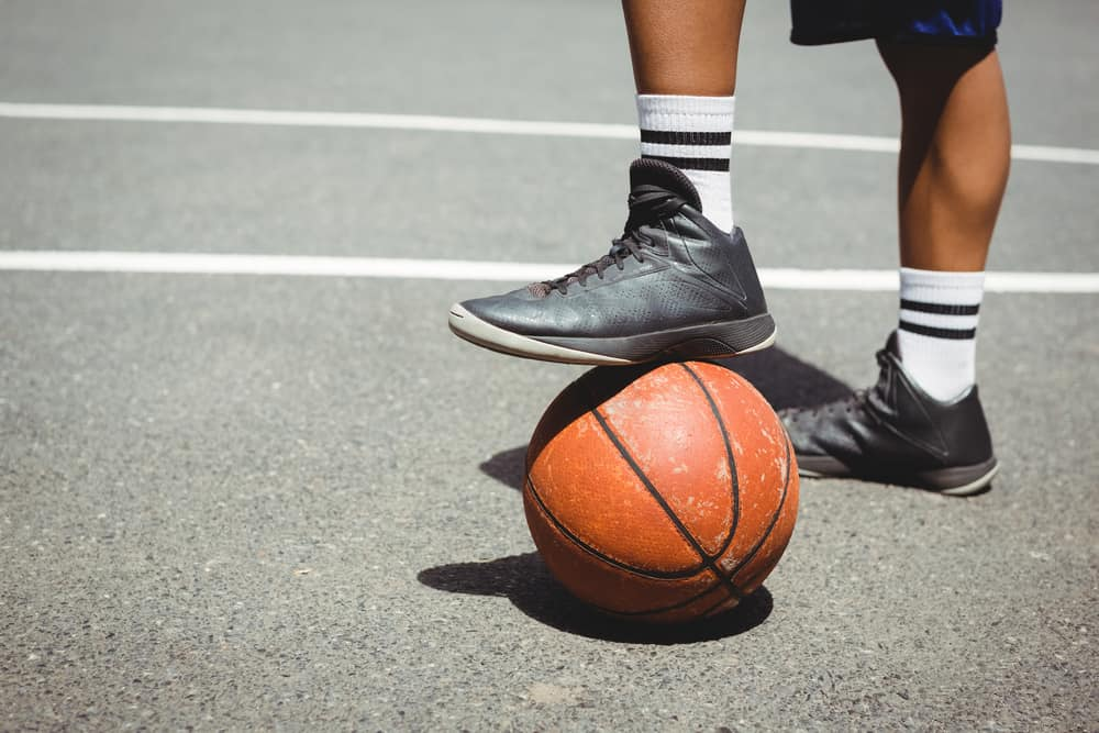 Man in mid-top basketball shoes standing with one leg on basketball.