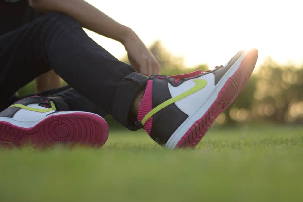 Man sitting in the park wearing a pair of Nike air Jordans.