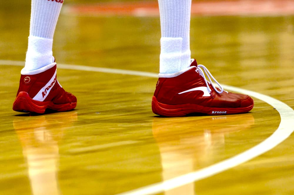 Basketball player wearing Nike red shoes during a game.