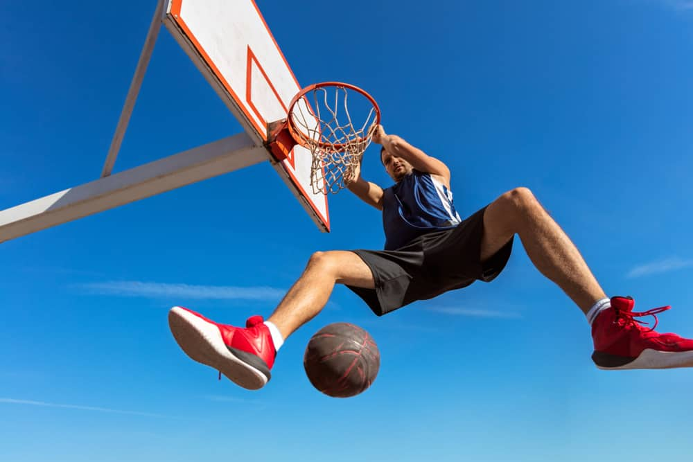Basketball player making slam dunk.