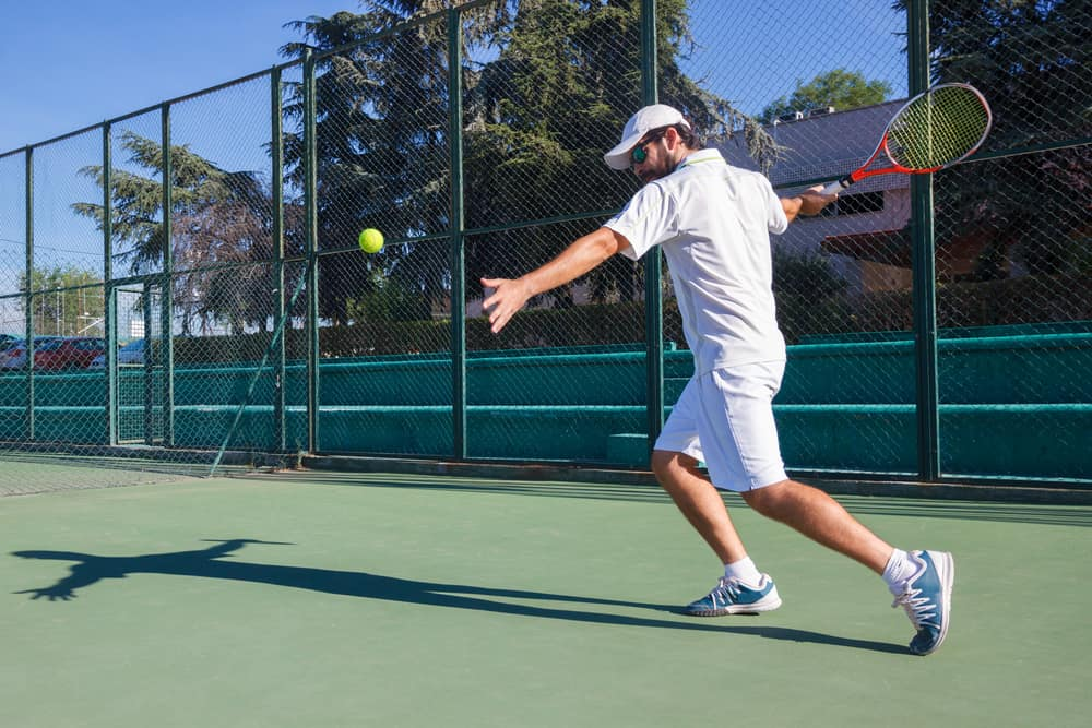 Man playing tennis on a court.