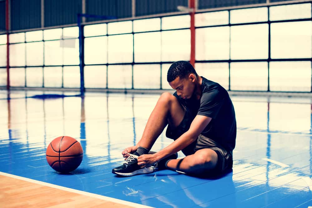Man tying his shoe laces on a basketball court.