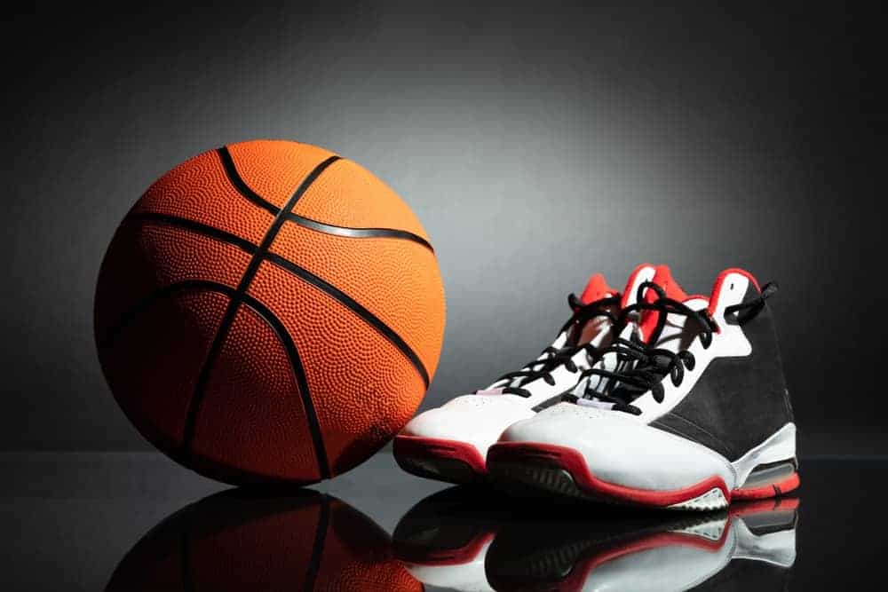 A pair of black and white basketball shoes with a basketball.