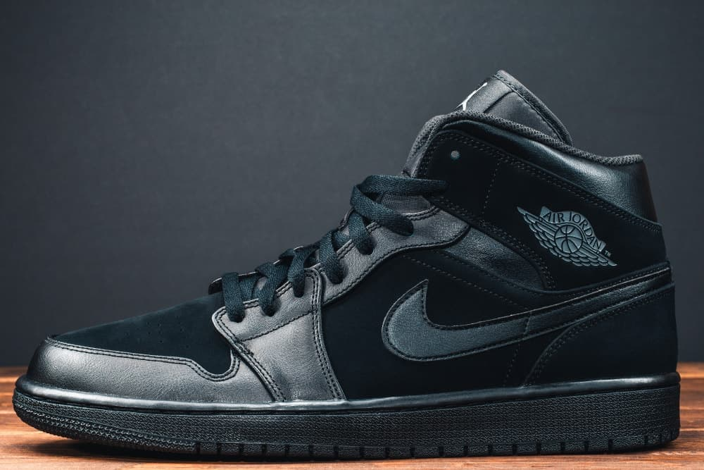 A close look at a pure black Mid-top basketball shoe.
