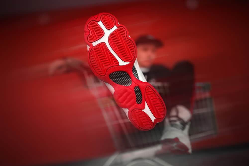 A close look at the bottom of a basketball shoe with red and white tone.