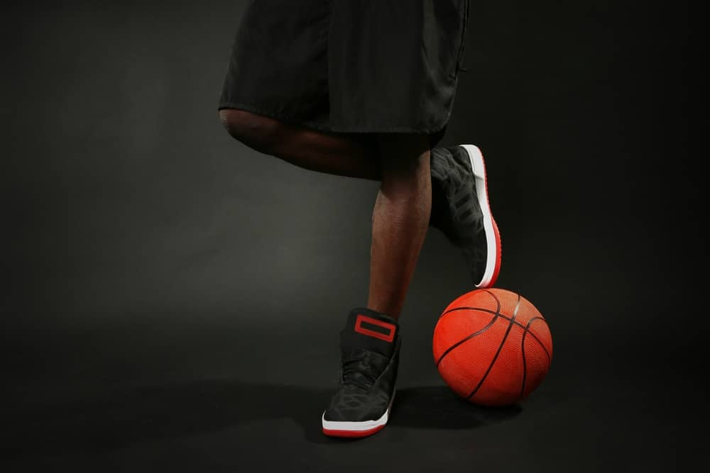 A man wearing a pair of black and red basketball shoes.