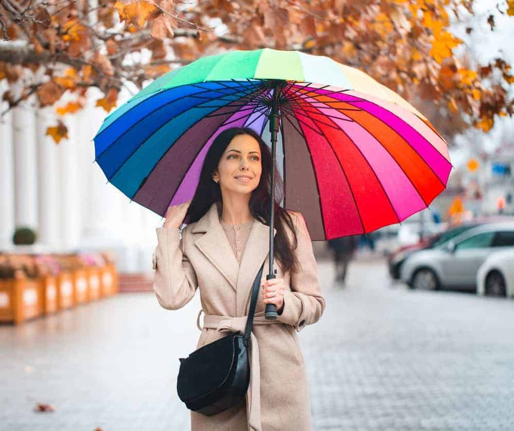 A woman wearing a trench coat with a colorful umbrella.