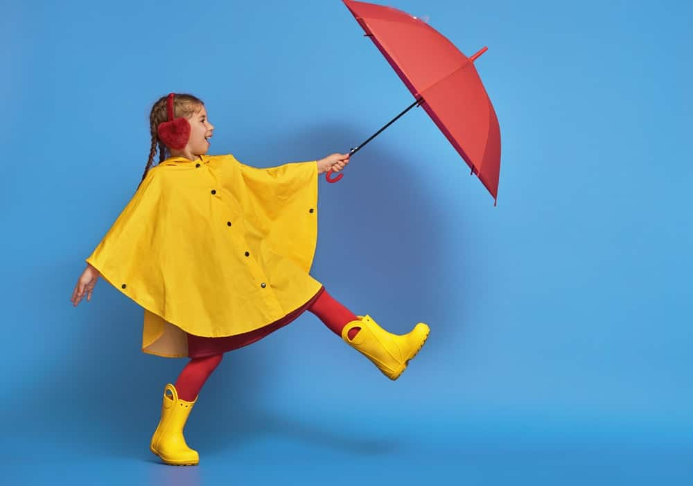 A girl wearing a yellow poncho raincoat that pairs with her boots.