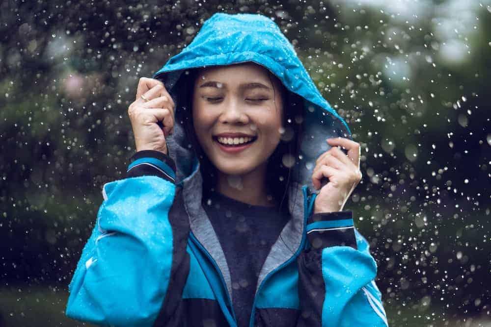 A woman wearing a blue rain jacket.