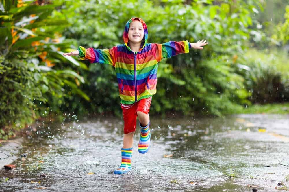 A boy wearing a rainbow jacket and boots.