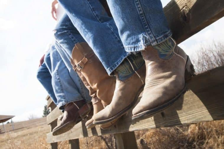 A row of cowboys wearing jeans and boots.