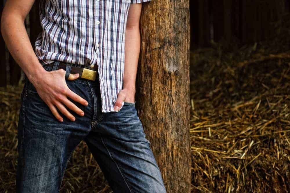 A man wearing cowboy jeans leaning on a tree.
