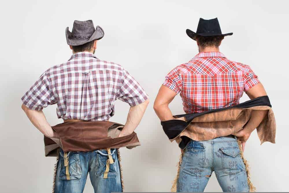 Two cowboys wearing jeans seen from behind.