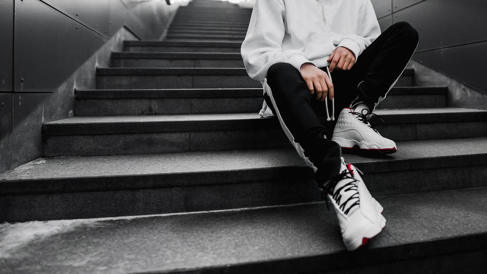 Man wearing basketball shoes sitting on stairs.