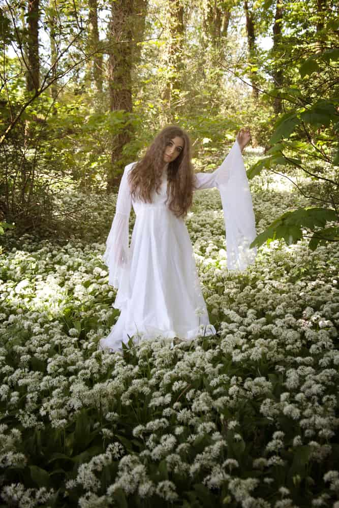 Woman in a forest wearing a white bell sleeve dress.