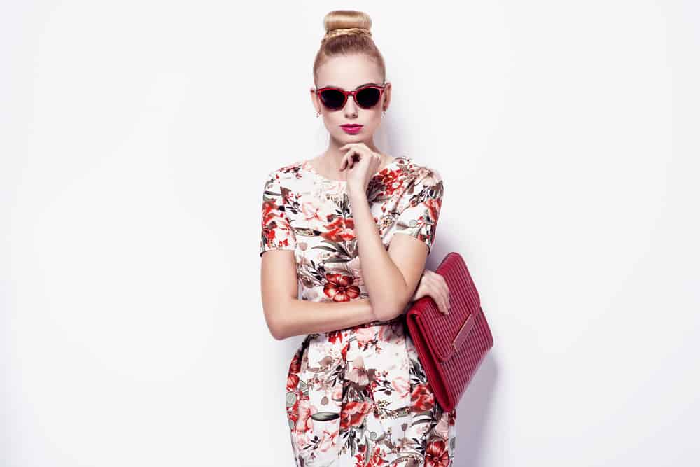 Model wearing a floral spring dress, sunglasses, and red purse.