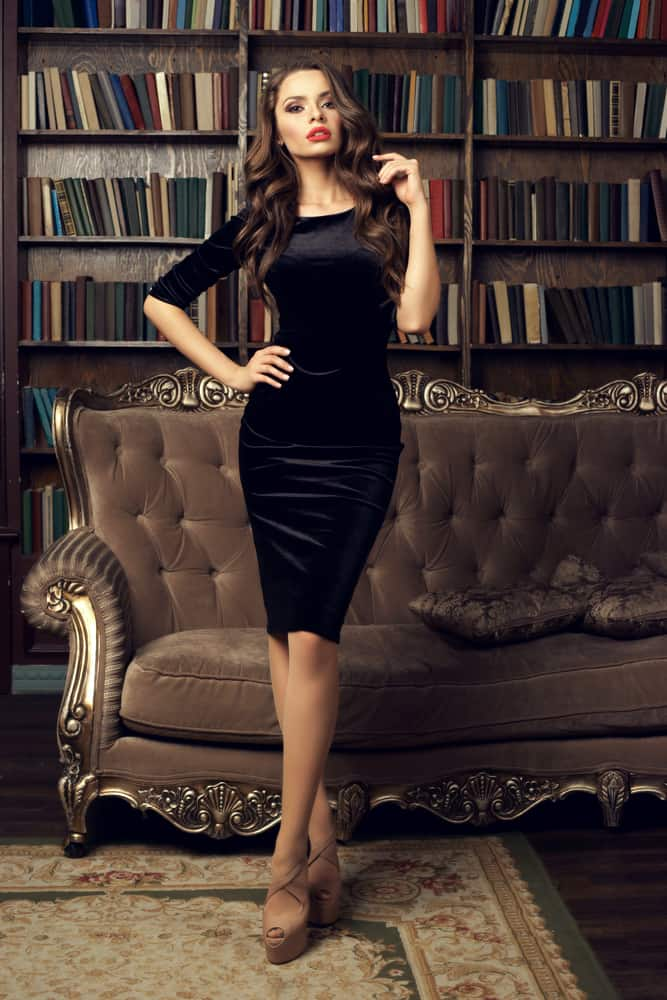 Woman in library wearing a black cocktail dress.