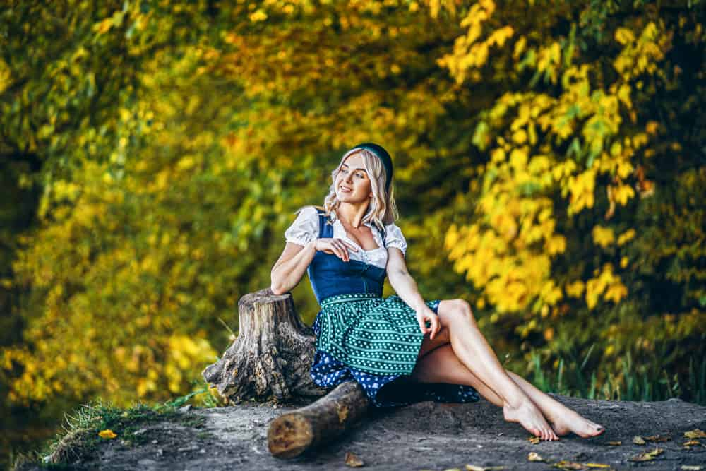 Woman in a green dirndl dress sitting outudoors.