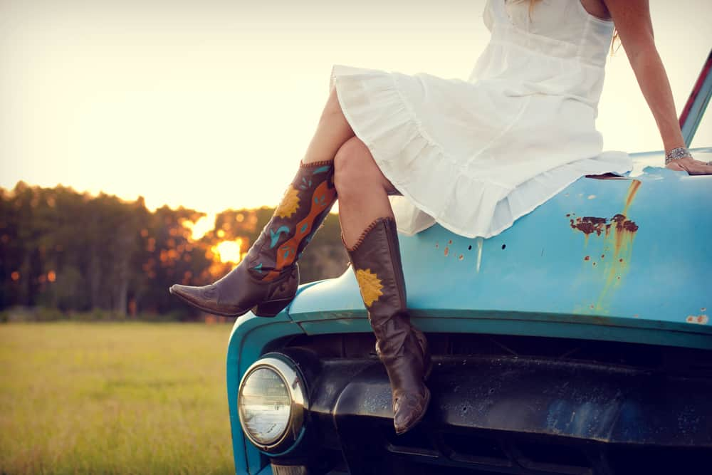Woman in white dress and boots sitting on a blue truck.