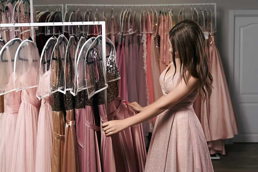 Model in a dressing room selecting an outfit.