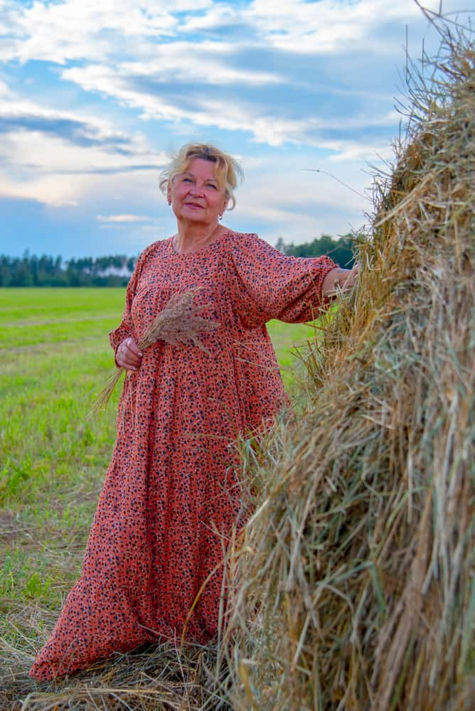 Elder woman with in a long country dress poses in haystacks.