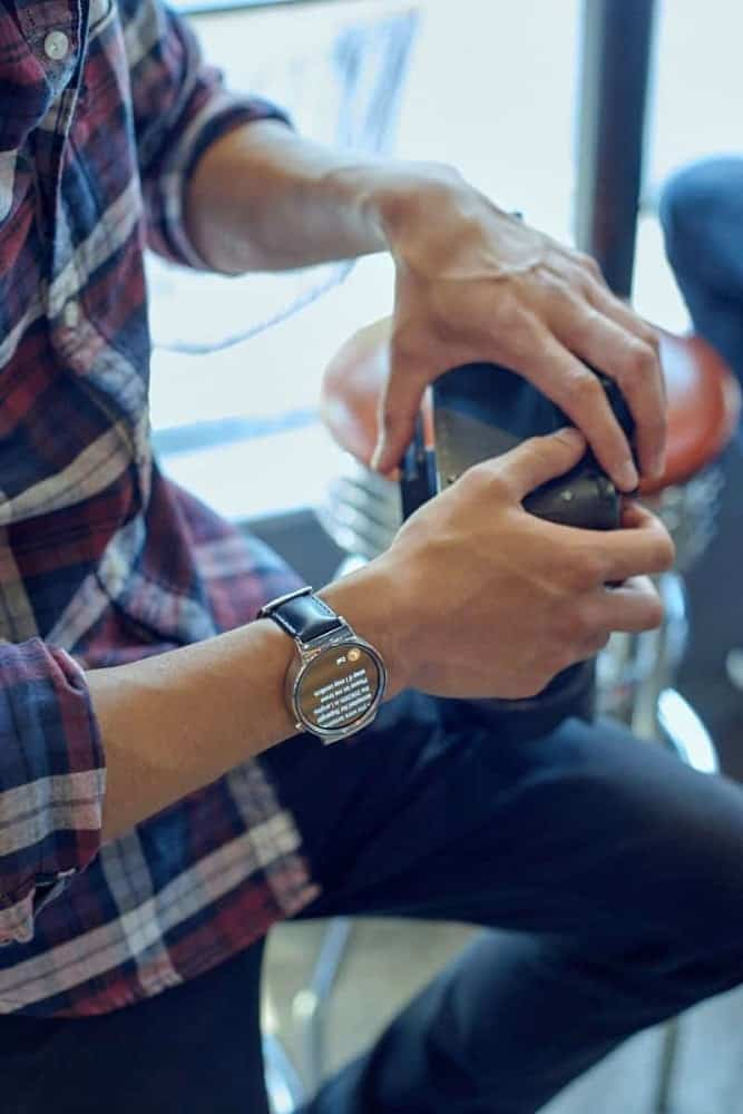 A man wearing a Huawei smartwatch showing messages.