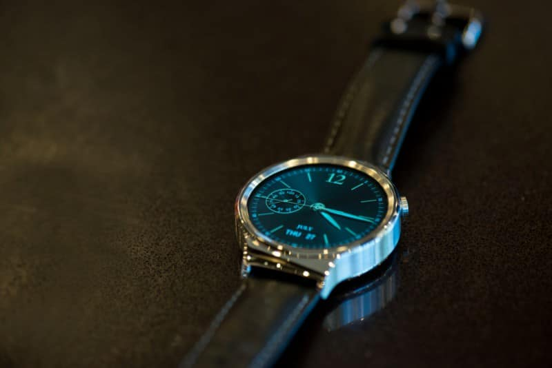 The Huawei smartwatch on a wooden table.