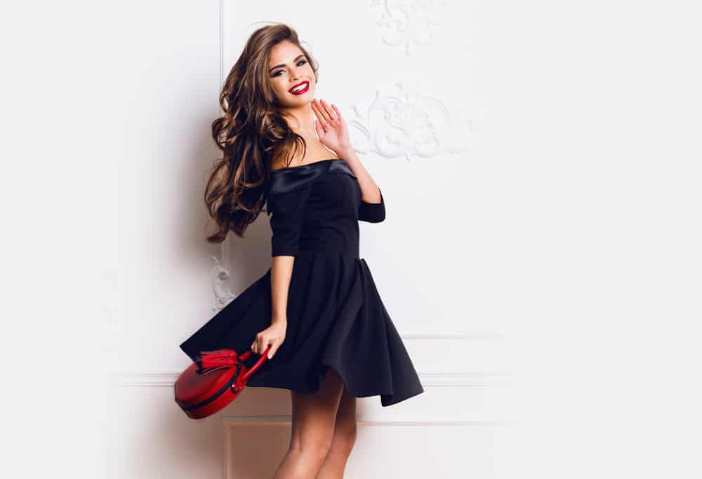 Woman in a little black dress and red handbag standing against a white wall.