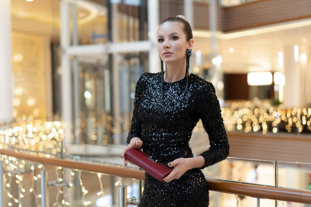 Woman in a shopping center wearing black sequin dress and a red clutch.